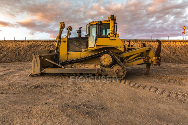Bulldozer on roadside of unpaved highway — Stock Photo