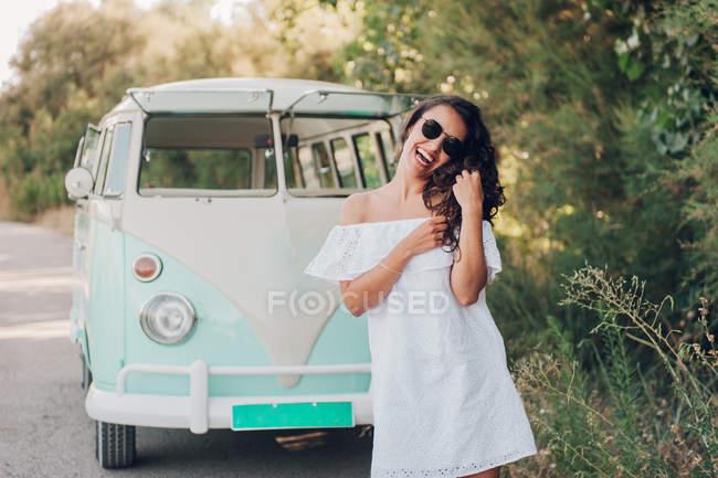 6f43f879a3 Alegre morena mujer en gafas de sol posando junto a la furgoneta en la  naturaleza -