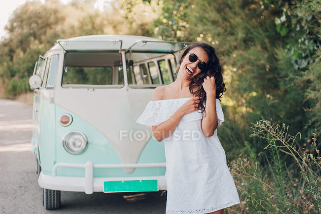 Cheerful brunette woman in sunglasses posing near van in nature — Stock Photo