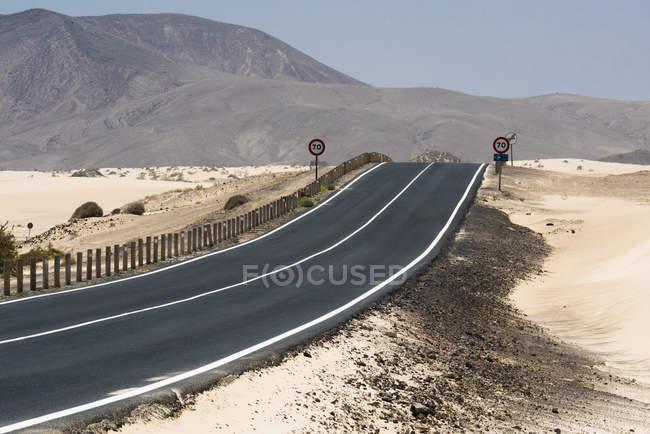 Autopistas y señales de tráfico en el desierto de Fuerteventura, Islas Canarias - foto de stock