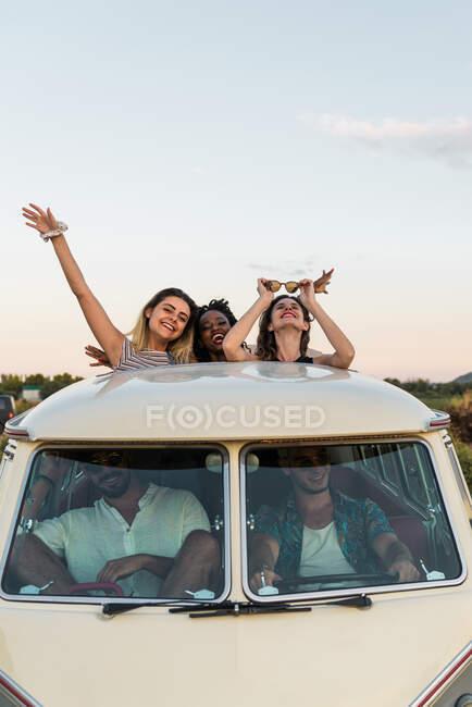Група різних молодих друзів стоїть в люку на даху вінтажного фургона і дивиться на камеру, проводячи разом час. — стокове фото
