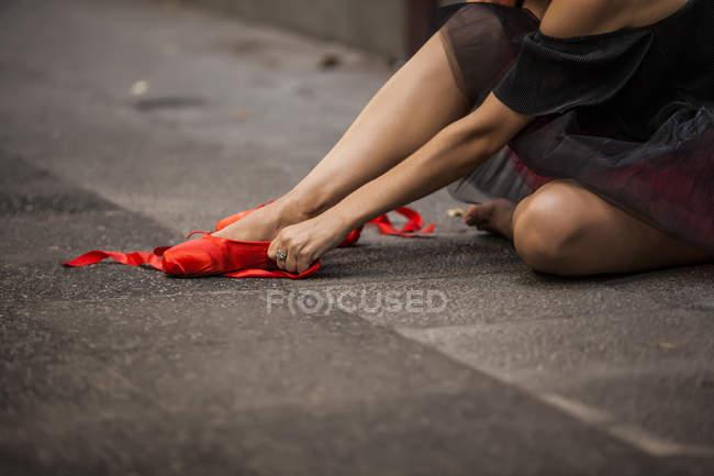 Image recadrée de ballerine avec tutu noir écrasant bouts de ballet rouge dans la rue — Photo de stock