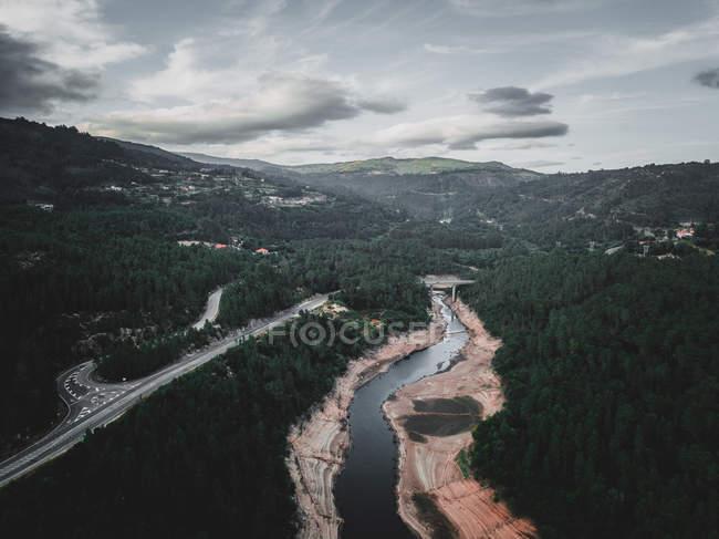 Drone vista del río tranquilo y camino angosto que atraviesa un espeso bosque en terreno montañoso en Galicia, España - foto de stock