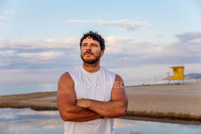 Homem adulto barbudo em sportswear em pé na praia durante o treinamento ao ar livre — Fotografia de Stock