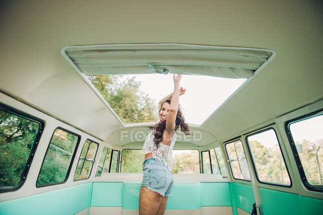 Mujer joven riendo y bailando bajo escotilla estando dentro van vintage - foto de stock