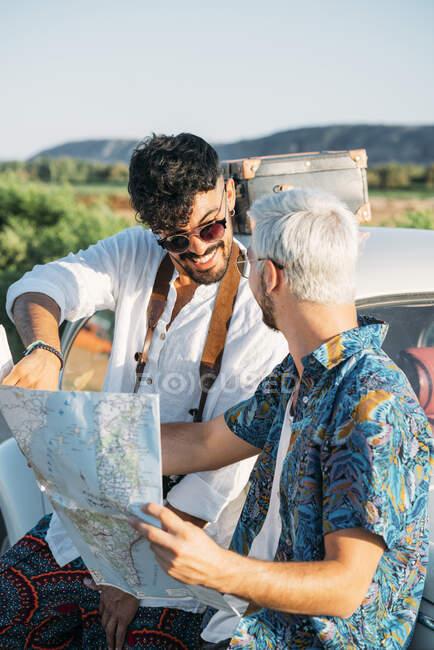 Due ragazzi giovani con macchina fotografica in piedi vicino auto retrò e guardando la mappa mentre viaggiano nella natura insieme — Foto stock