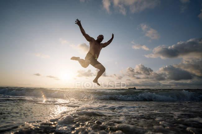 Silhouette dell'uomo che salta sulla spiaggia — Foto stock