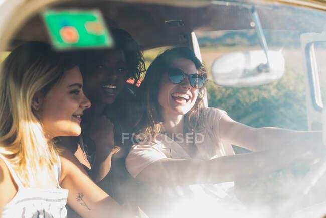 Группа счастливых мультиэтнических женщин в автомобиле едут вместе под ярким солнцем и смеются — стоковое фото