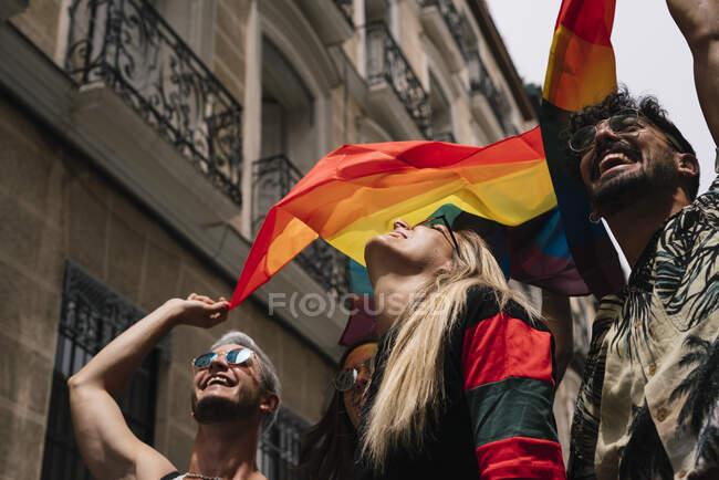 Группа друзей с флагом гей-гордости в городе Мадриде — стоковое фото