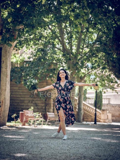 Heureuse femme brune souriante tenant un bouquet de fleurs et debout dans un parc ensoleillé avec les mains écartées — Photo de stock