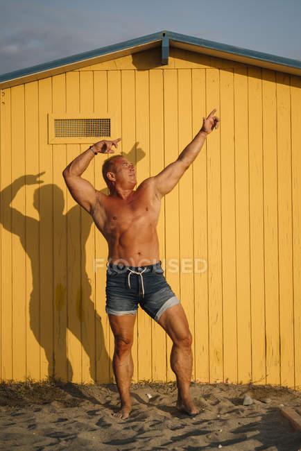 Muskulöser älterer Mann posiert vor gelbem Hintergrund — Stockfoto