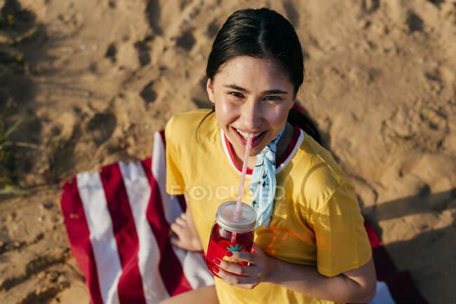 Ragazza casual con bevanda sulla sabbia — Foto stock