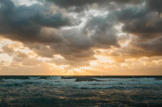 Luminoso sole che tramonta sul mare ondulato dietro spesse nuvole a Miami — Foto stock