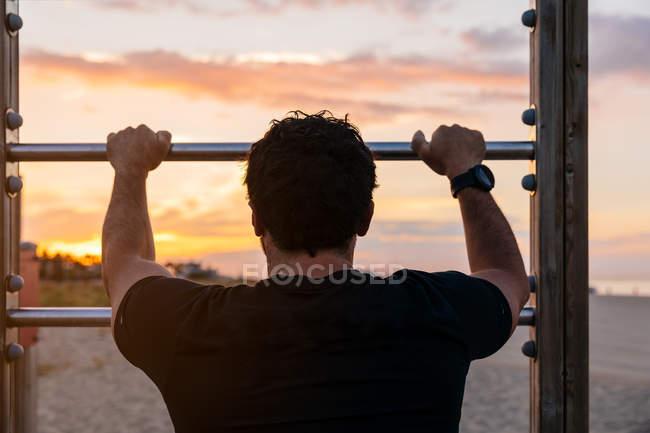 Мужчина в спортивной одежде опирается на лестницу во время тренировки на пляже на закате — стоковое фото