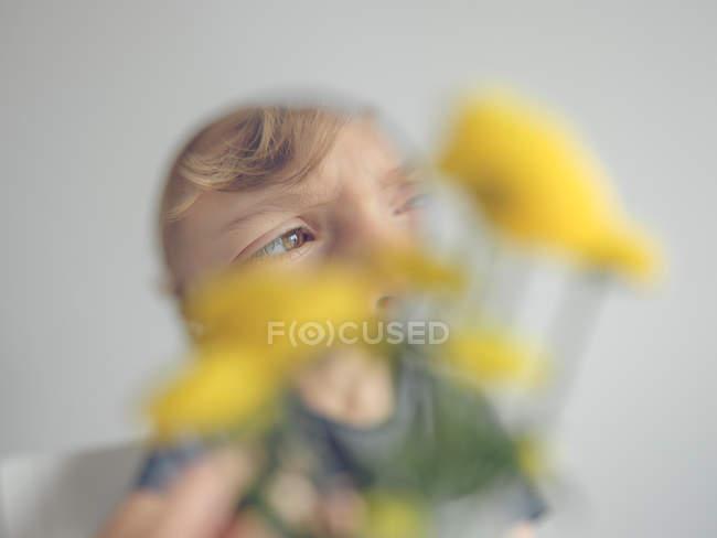 Garçon avec loupe regardant les pissenlits — Photo de stock