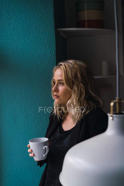 Романтичний вдумливі жінка з склянки напою в домашніх умовах — стокове фото