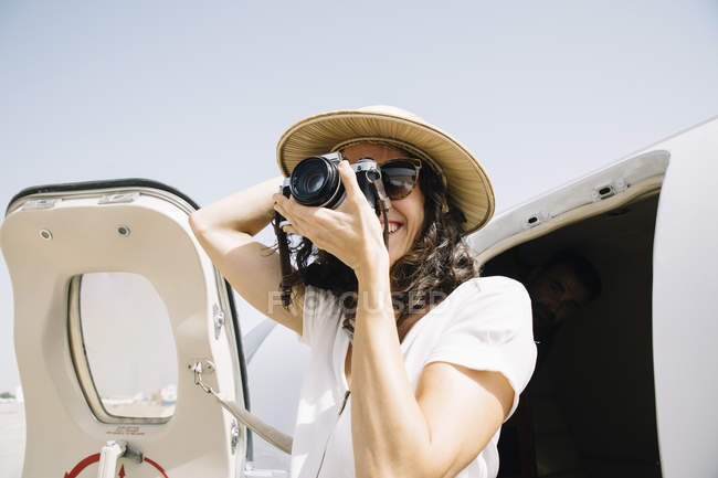 Female traveler standing near airplane and taking photo — Stock Photo