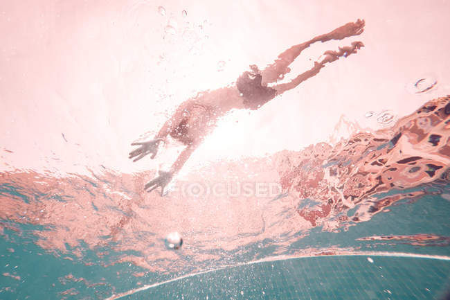 Silhouette of swimming child in transparent pool surrounded by light of sunbeams — Stock Photo