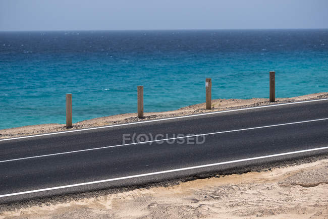 Fenced by wooden poles highway on ocean coastline with blue water in daytime, Canary Islands — Stockfoto