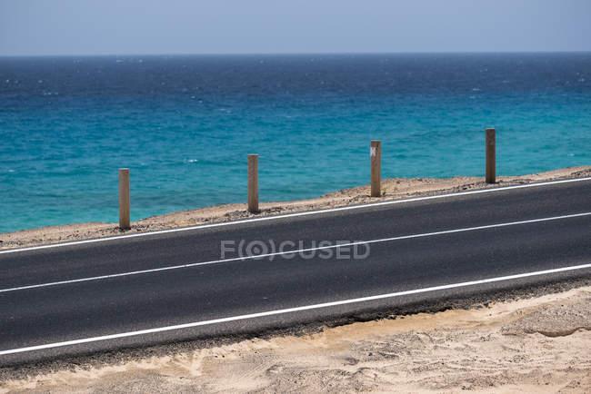 Огороженная деревянными столбами шоссе на побережье океана с голубой водой в дневное время, Канарские острова — стоковое фото
