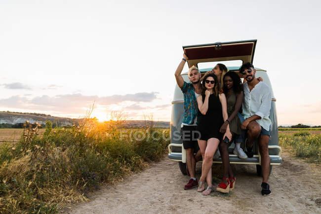 Группа веселых молодых людей, стоящих рядом с фургоном ретро и смеющихся, проводя время на природе вместе — стоковое фото