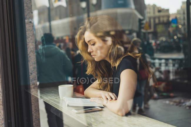 Молодий зосереджено жінка читання книги в кафе — стокове фото