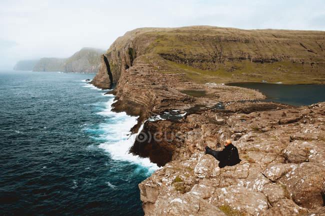 Туристы, сидя на скале рок и смотреть на океан, Фарерские острова — стоковое фото