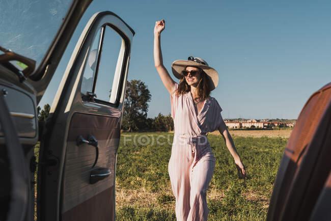 Вид изнутри ретро-автомобиля счастливой трехлетней женщины в шляпе и солнцезащитных очках, взволнованно стоящей на природе и смеющейся — стоковое фото