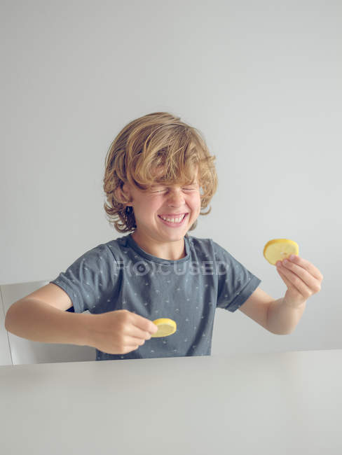Chico divertido con rodajas de limón - foto de stock