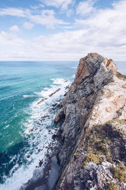 Amazing view of sea water splashing near long rocky cliff on cloudy day in Asturias, Spain — Stock Photo