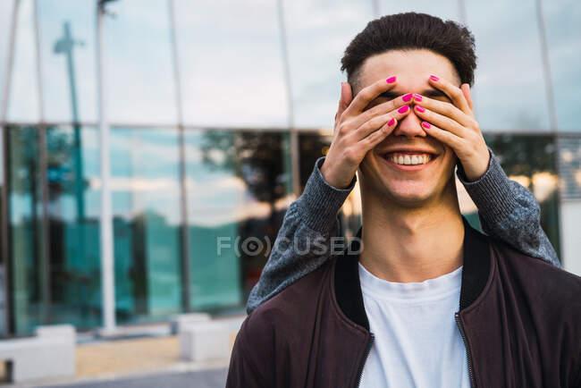Анонімна жінка, яка стоїть позаду щасливого стильного чоловіка, закриваючи очі.. — стокове фото
