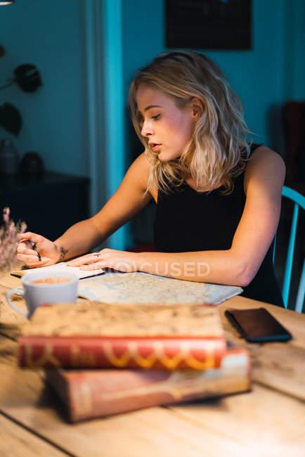 Femme blonde assise à table avec des livres, carte et café et planification de voyage — Photo de stock
