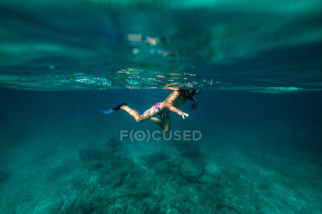 Anonymous boy snorkeling in dark sea water — Stock Photo