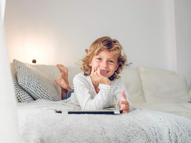 Entzückender Junge mit lockigem Haar blickt in die Kamera, während er auf einer bequemen Couch in der Nähe von Kissen mit digitalem Tablet liegt — Stockfoto