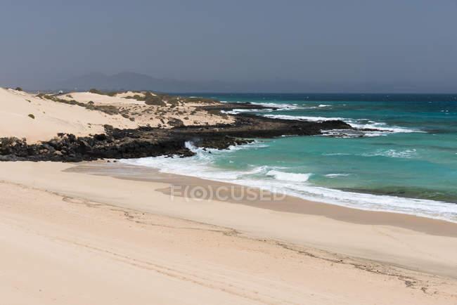 Шорлайн океана с голубыми волнами воды и песком со скалами с туманными горами, Канарские острова — стоковое фото