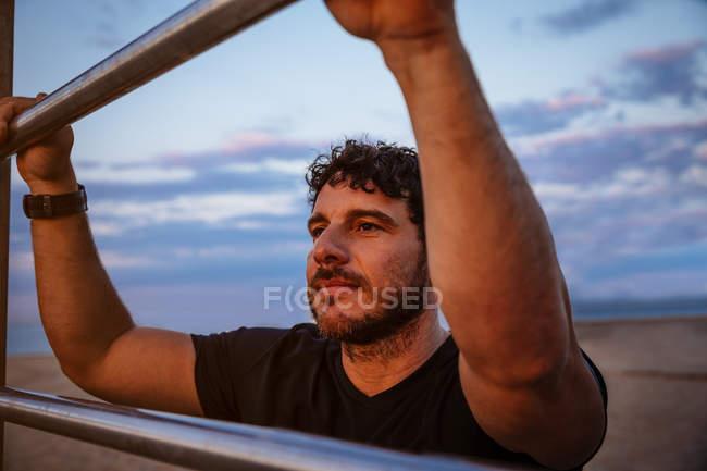 Homem barbudo em sportswear inclinado na escada e olhando para longe enquanto descansa durante o treinamento ao ar livre — Fotografia de Stock
