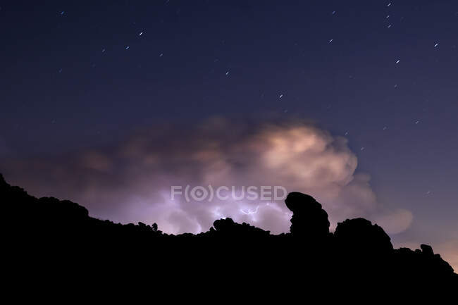 Rays and clouds in night storm over the mountain under a starry sky — Stock Photo