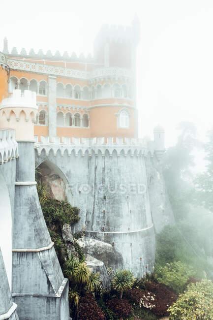 Внешний вид средневекового экзотического замка на скале с зеленым садом внизу в тумане, Синтра, Португалия — стоковое фото