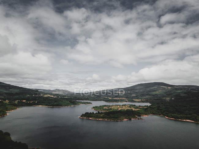 Vue par drone de nuages blancs flottant sur une rivière calme et des collines verdoyantes dans la belle campagne de Galice en Espagne — Photo de stock