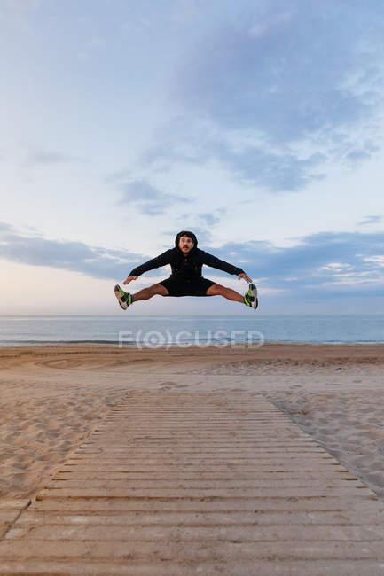 Активный человек в спортивной одежде, прыжки высокой открытый тренировках на песчаном пляже — стоковое фото