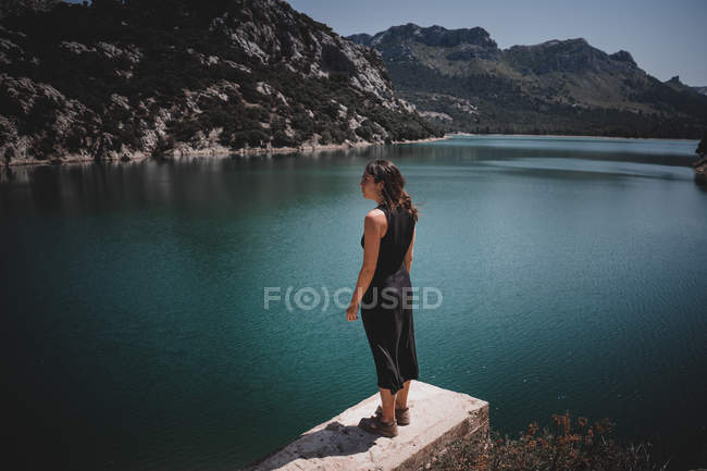 Side view of young woman in black dress standing on stone border and admiring view of calm sea in Mallorca, Spain — Stock Photo