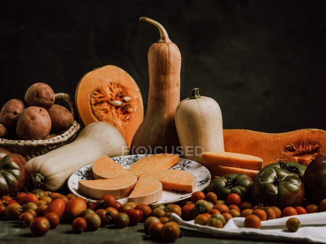 Beautiful warm arrangement of ripe butternut squashes on table with tiny tomatoes and plate with slices — Stock Photo
