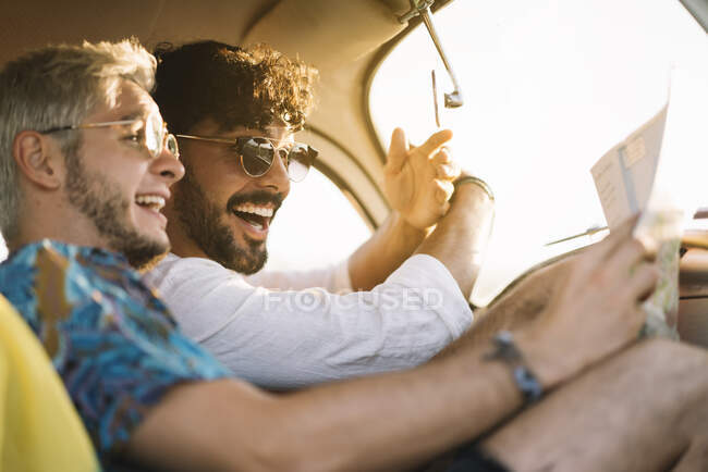 Two young guys laughing and holding map while sitting inside retro car during nice travel — Stock Photo