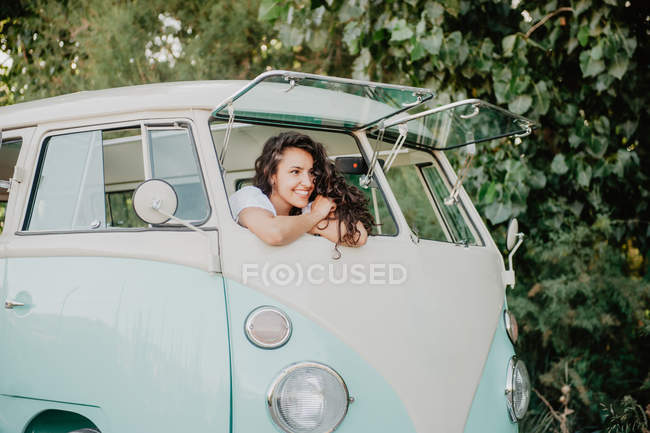 Smiling young woman leaning out windscreen of retro van while traveling in nature — Stock Photo