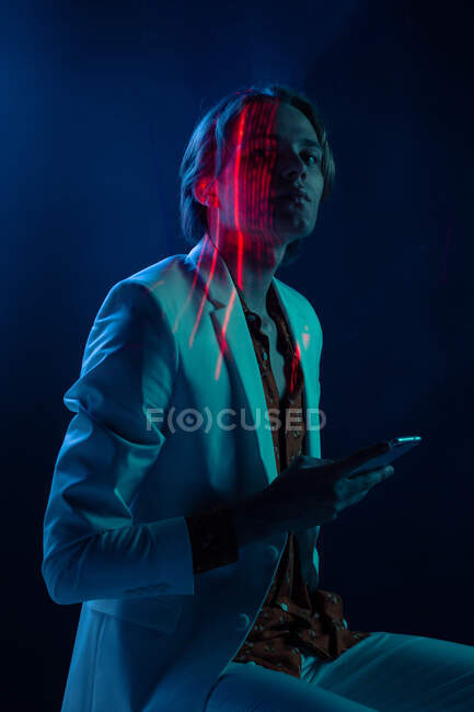 Abstract projection of face of attractive androgynous man in suit using smartphone in dark room — Stock Photo