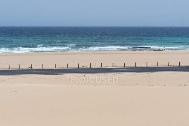 Огороженная автомагистраль на песчаной равнине с побережьем с бесконечным голубым восковым океаном, Канарские острова — стоковое фото
