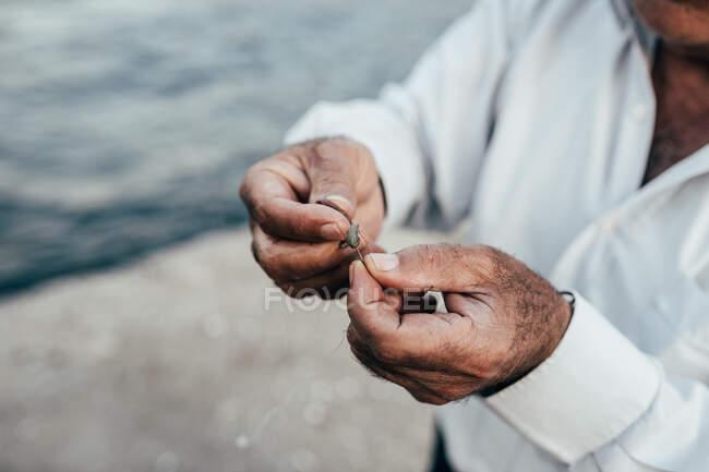 Mãos de colheita de homem étnico irreconhecível segurando mergulho e se preparando para a pesca na água — Fotografia de Stock