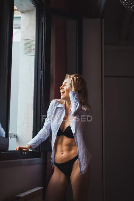Laughing sensual woman in lingerie and shirt leaning at window — Stock Photo
