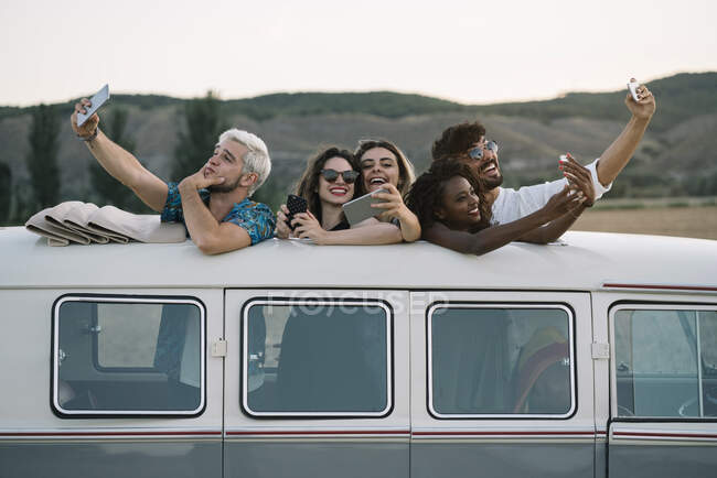Group of cheerful diverse people standing inside vintage van with opened roof and posing for selfie while travelling in countryside together — Stock Photo