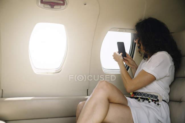 Donna che scatta foto attraverso la finestra dell'aeroplano — Foto stock